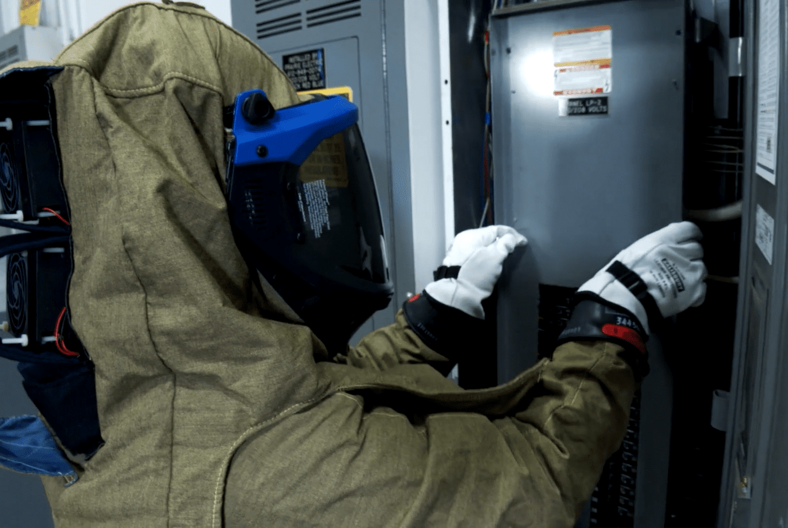Integrated Building Solutions technician near electrical box performing arc flash services.