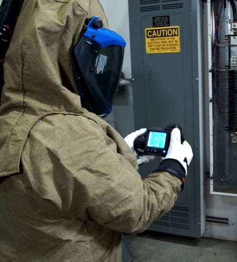 Integrated Building Solutions technician using infrared radar camera to service an electrical panel.